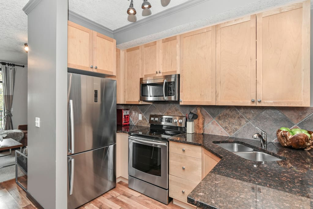 Fully stocked kitchen with new stainless steel appliances.