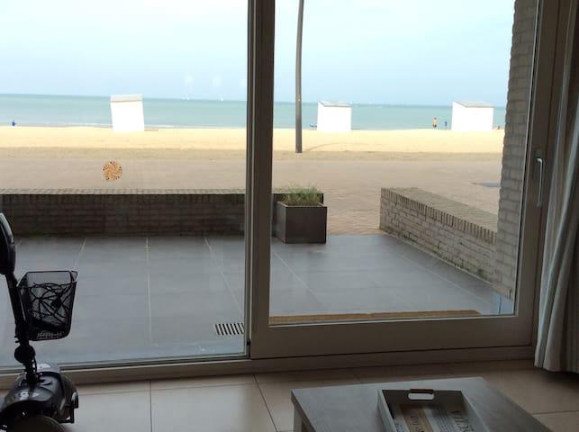Un appartement rez-de-chaussée face à la mer avec une terrasse privée devant et en arrière.