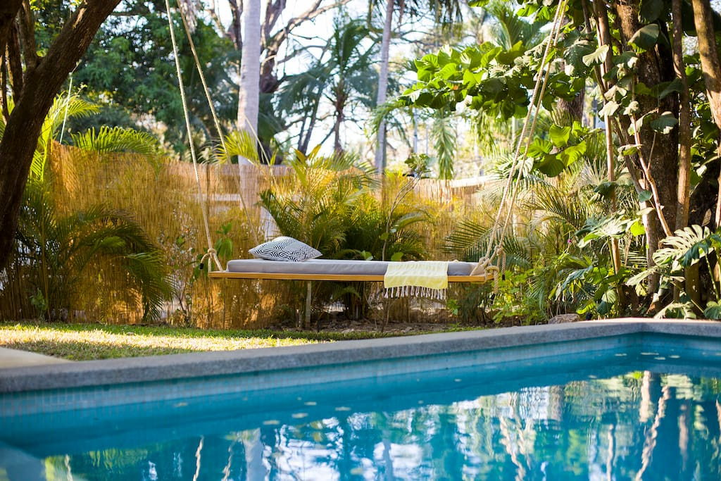 Relax in the hanging bed in the shade by the pool to escape the mid-day heat