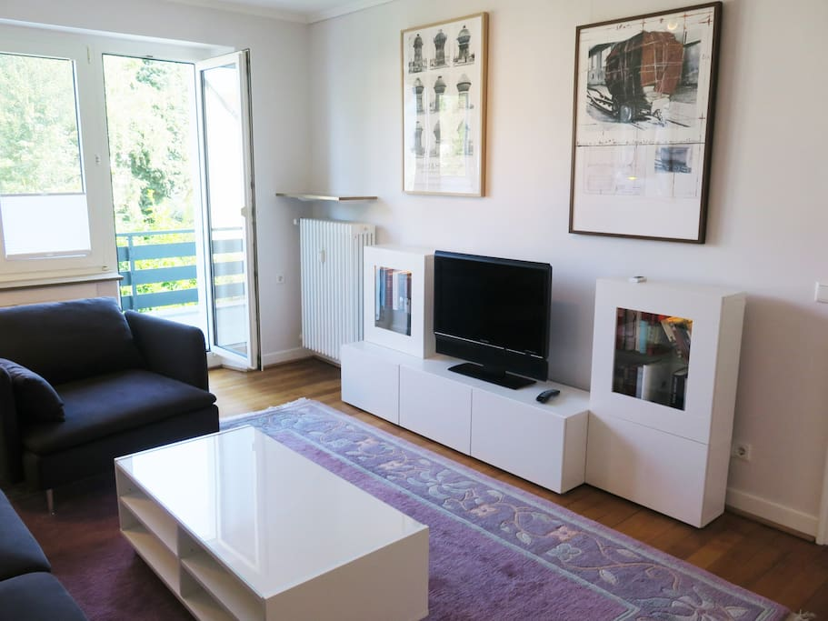 Wohnzimmer mit Balkonzugang und LED-TV