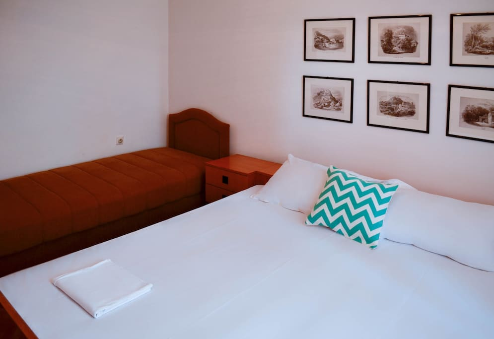 The room features one double bed and one single bed.