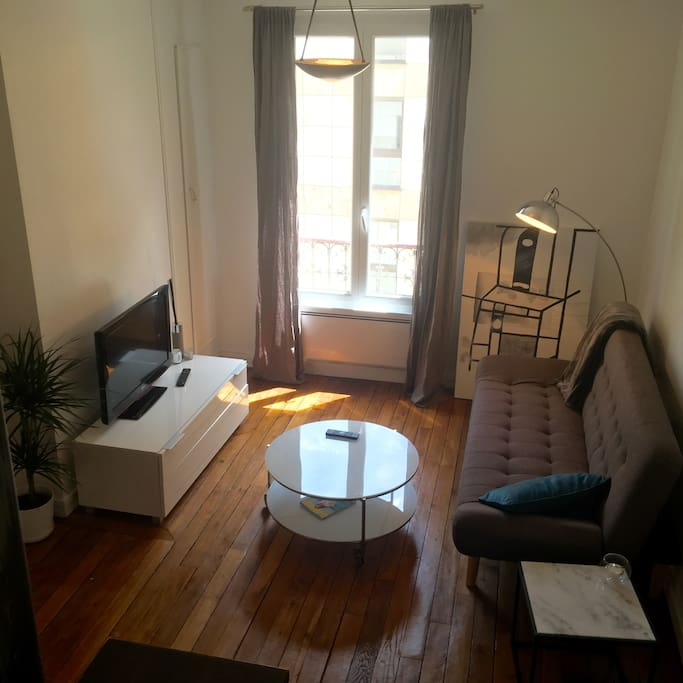 Living room with moulding and wooden floor. Equiped of a large TV, wifi, a sofa bed, heater.
