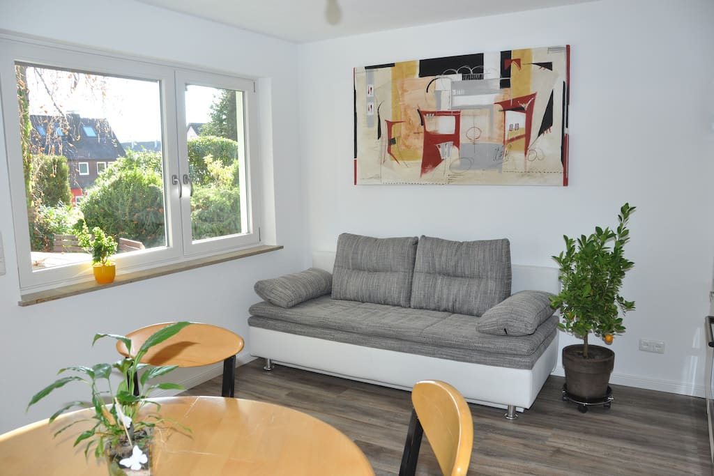 heller Wohn- und Essbereich mit einer Küchenzeile. Das Funktionssofa liefert neben dem Doppelbett im Schlafzimmer, eine zusätzliche Schlafmöglichkeit für 2 Personen (ebene Liegefläche mit 160 x 200 cm)