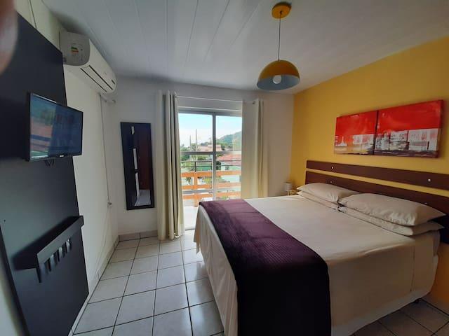 Apartamento 5. Quarto de casal com tv, ar condicionado e sacada.