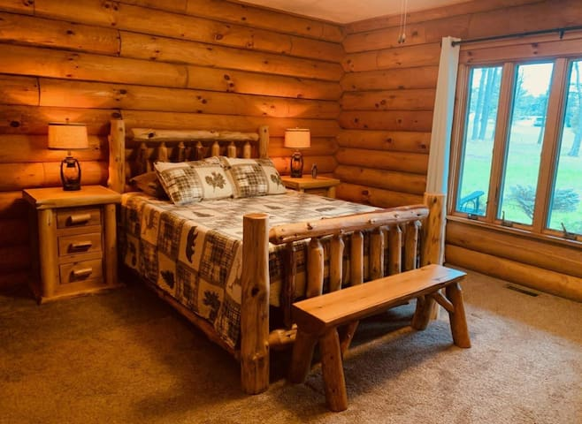 Master Bedroom features a queen size bed, log furniture, beautiful full window view and attached Master Bath and Shower.
