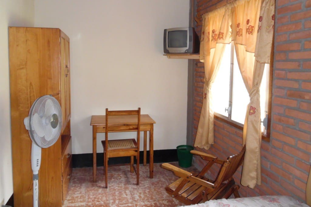 Inside family room with small desk, cable color TV, wardrobe and floor fan