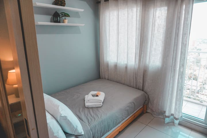 Double size bed with pull out facing the amenities and Makati Skyline