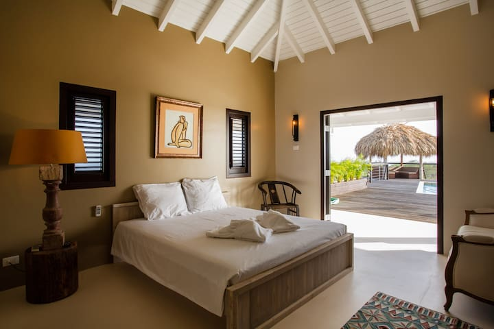 Master bedroom with direct entrance to pool and private bathroom.