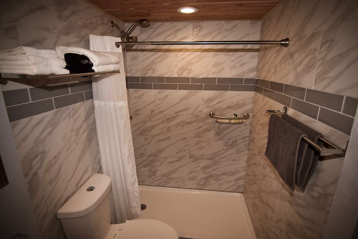 Newly remodeled bathroom includes shower pan, wall to ceiling tile,  glass vanity and bowl sink, and decorative tile flooring.   Cedar ceilings throughout the bathroom give you that fresh cedar smell after a hot shower. (Pressure is not always ideal)