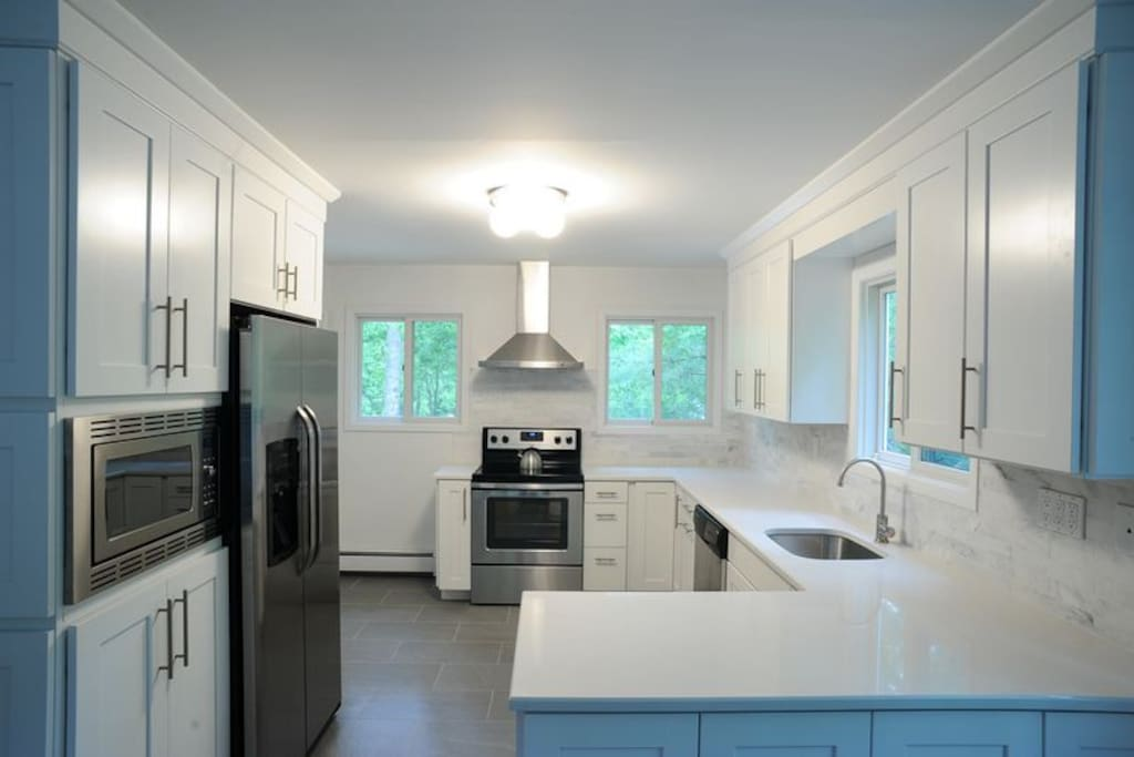 Modern new kitchen with white quartz countertops, stainless steel appliances, and slate tile floor.