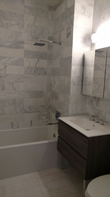 All marble, pristine, new bathroom with rain shower.