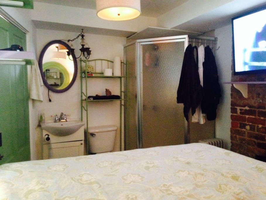 Bathroom near bed with no divider.