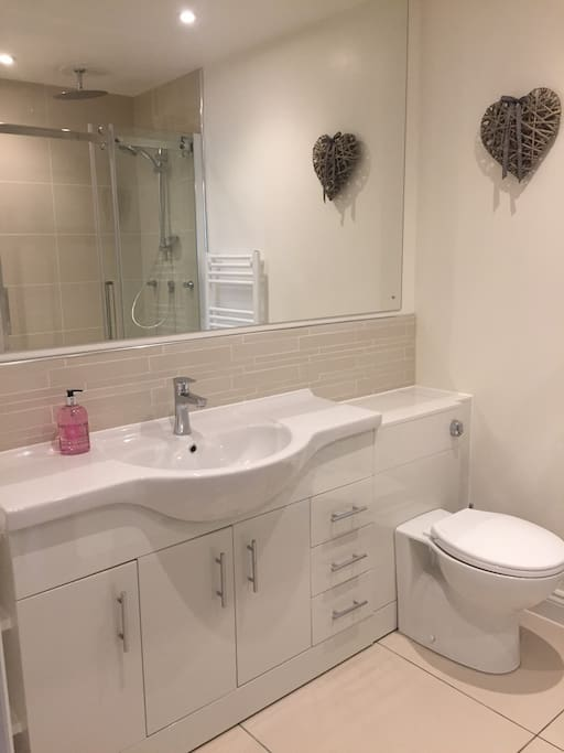Bathroom sink and toilet with shaver socket, mirror and storage. Large heated mirror when bathroom lights go on.