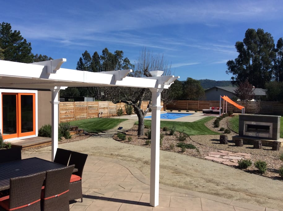 Pergola - seating for 8, cabana/playroom to left, pool and sail shade ahead, outdoor fireplace