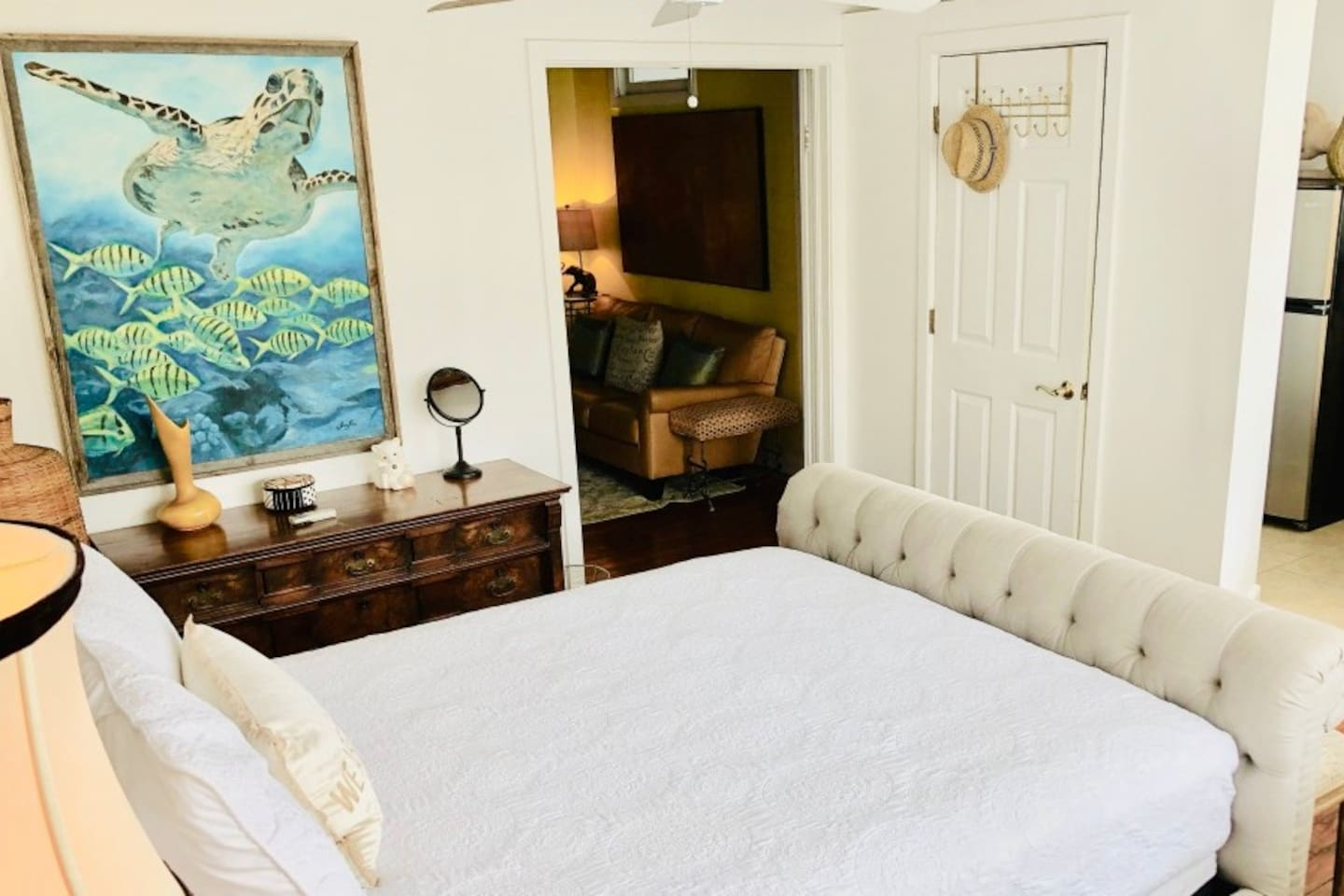 Queen sized bed with lots of windows & natural light. Doors open showing Living Room. Closet doors & just around the corner is the kitchen & bathroom with 1950's Sarasota School of Architecture details. Painting by Sarasota Chalk Festival Artist.