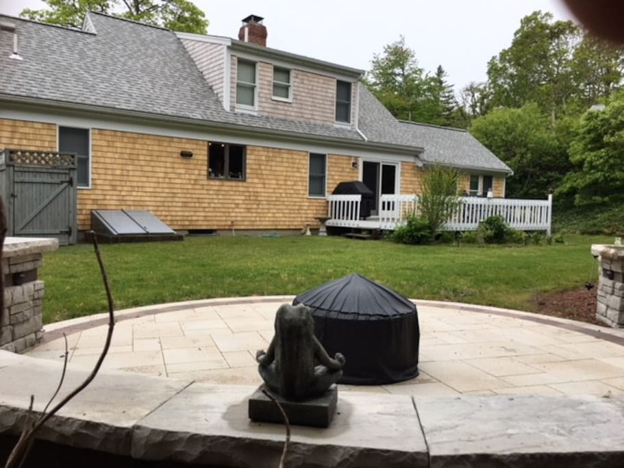 Private back yard with outdoor shower, large back porch, and new patio with sitting wall and fire pit area