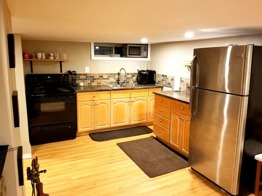 Kitchen with New Fridge and Stove.  Keurig Coffee Maker (with Coffee) Milk and Sugar