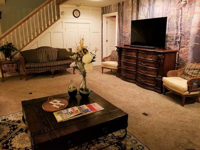 """Large family room,  two captain side chairs, large heavy wooden/iron coffee table, Ethan Allen goose down filled loveseat.  Three extra bunch tables,  Game side table, overhead lighting and side lighting. 55"""" Smart TV with sound bar, AM/FM/CD player."""