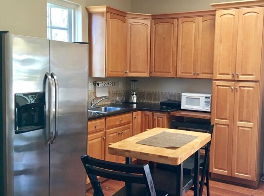 Full size fridge, granite counters, cook-top, microwave, and oven