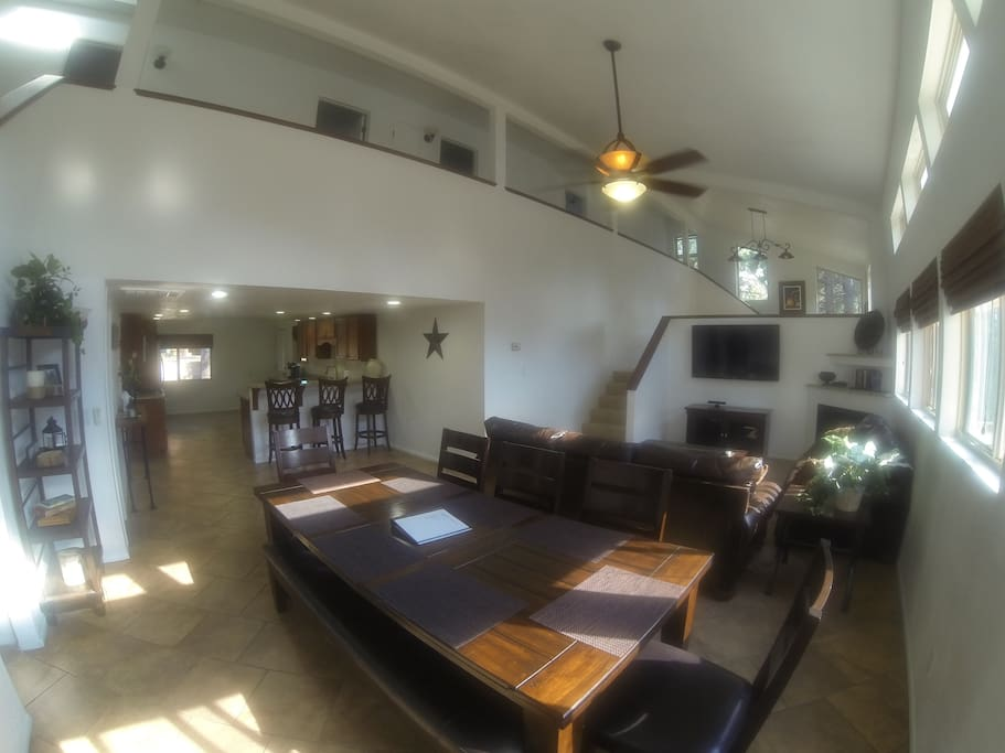 Great room with farmhouse dining table, leather couches, and open to the kitchen