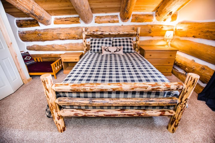 The other upstairs bedroom has a queen log bed and a toddler bed.
