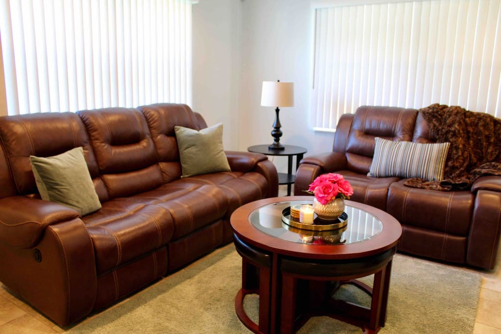 Living room with sofa and love seat. The large sofa reclines for extra relaxation.