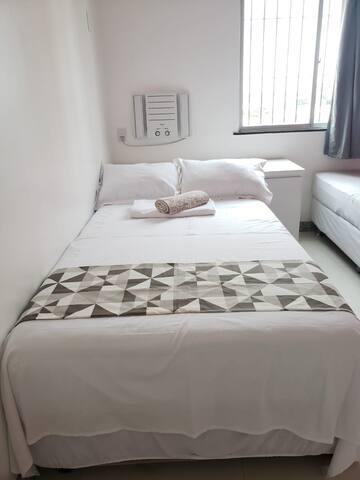 Quarto com cama solteirão e cama de solteiro com ar condicionado.