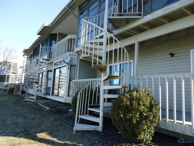 Spiral staircase from enclose porch goes down to a 30 foot boat dock