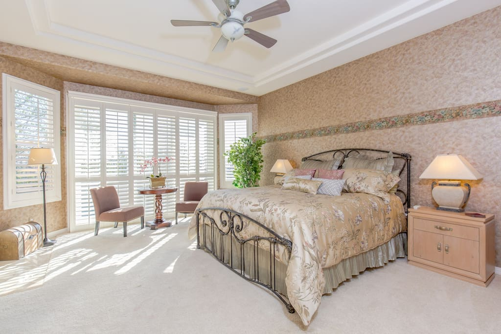 Master Suite has sliding glass door out to the pool, king size bed, mirrored closet, table and chairs, light-switch-on gas fireplace, connected bathroom w/ romantic & luxurious deep bath tub next to the two sided fireplace, dual sinks, and mirrored walk in closet.