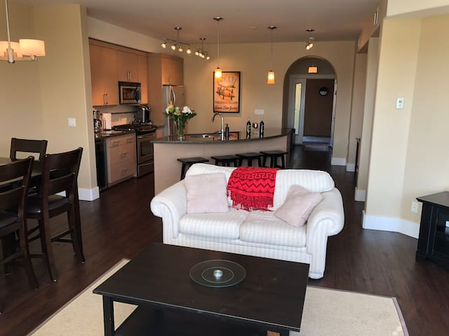 Large open-concept living, dining and kitchen with dining table, breakfast bar, two couches and TV. Note: the white furniture has just been updated to leather sofa and loveseat. See more pictures...