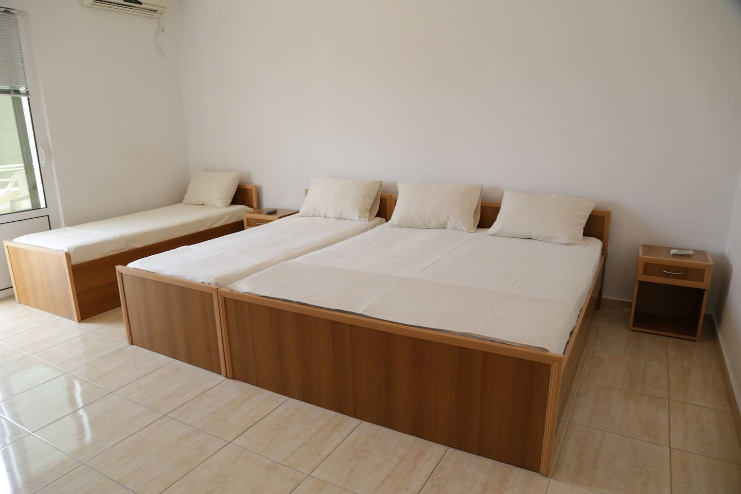 Room for four persons with one double  and two single beds with nightstands and balcony overlooking garden