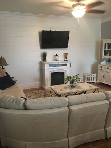 White sectional living-room with 50in smart TV and cozy electric fireplace