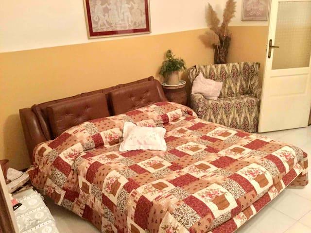 Camera da letto 3 con divano letto doppio, comodini e lampada, un divano, un tavolo, 4 sedie, una parete attrezzata uno specchio, e un ampio balcone con vista stupenda.