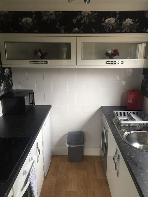 Kitchen with all the essentials, cooker, fridge, washing machine and microwave.