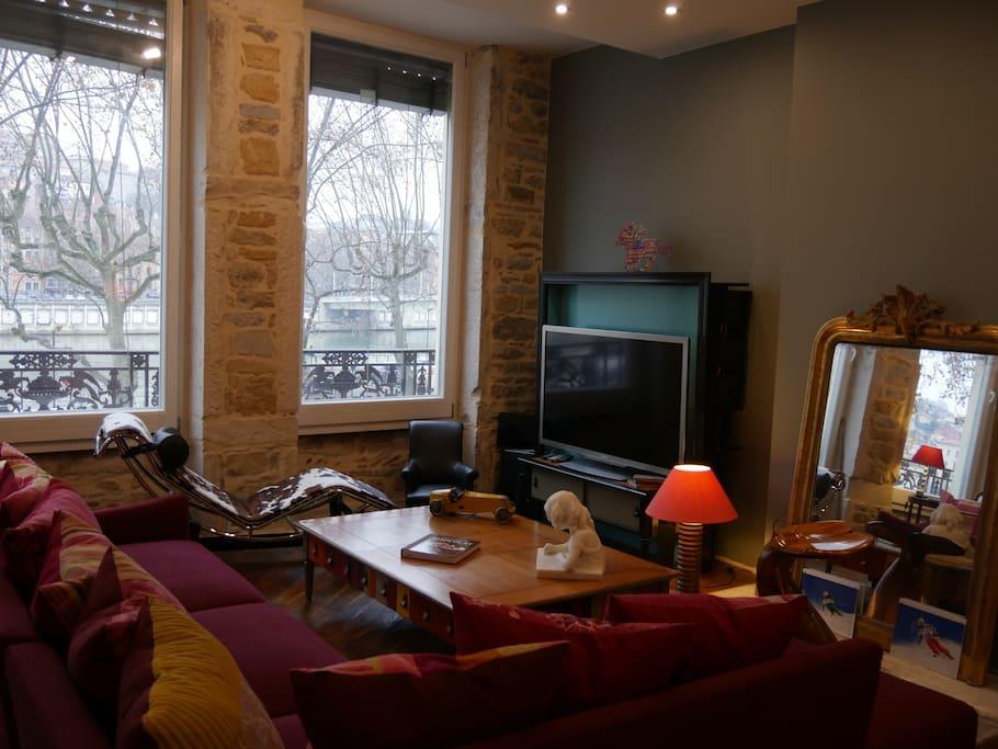une grande pièce de vie avec une vue magnifique sur la Saône, le palais de justice et Fourvière.
