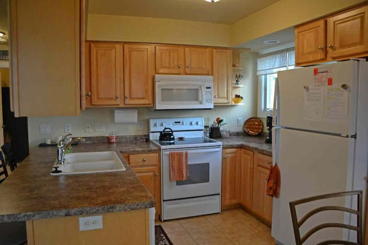 Fully equipped kitchen - stove, refrigerator, microwave, coffee maker, toaster, pots and pans, dishes, utensils.