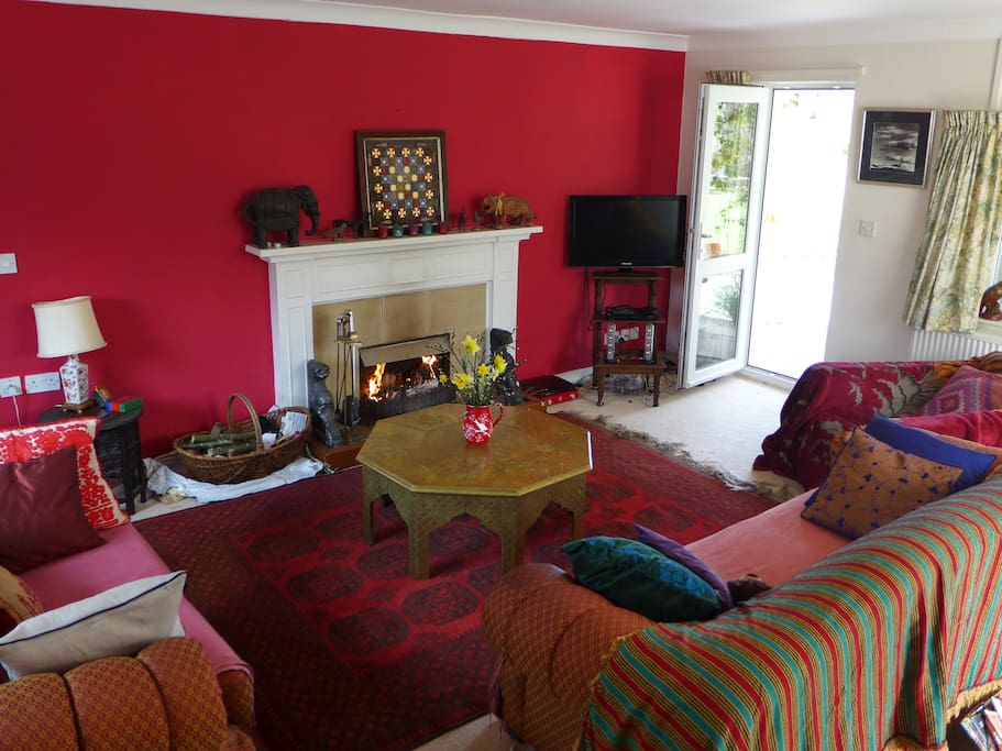 The living room, with an open fire and lots of books, opens directly onto the gardens.