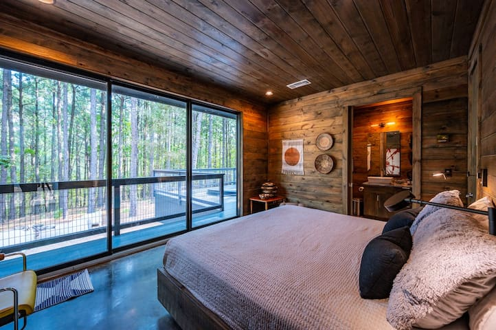 The guest bedroom has it's own private deck and forest views.  There is also (pictured in next picture) a small desk incase some work has to be done as well as a closet for storage.