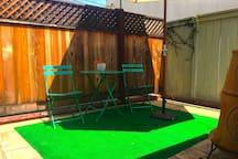 Sunny private patio with bistro table and umbrella