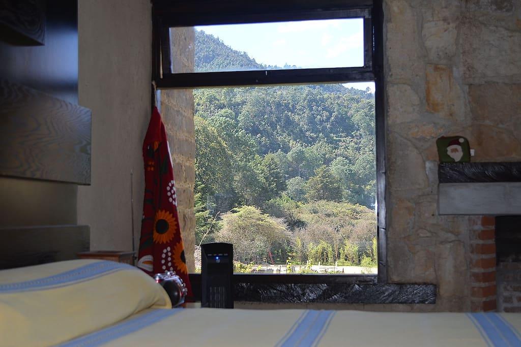 Recamara principal con chimenea y  calentador eléctrico. Ventana hacia el jardín y la montaña.