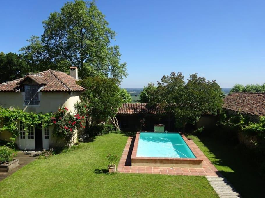 Vue sur le jardin clos et la piscine depuis la maison. À l'arrière-plan, la vallée de l'Adour.