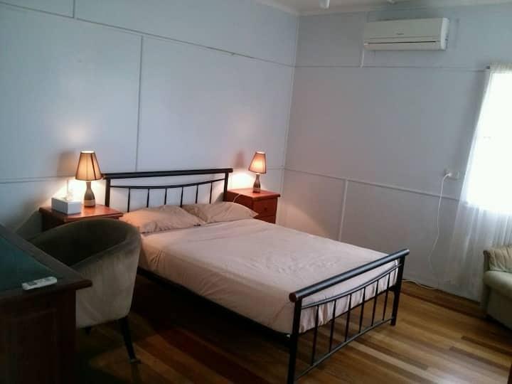 Large bedroom with bar fridge .