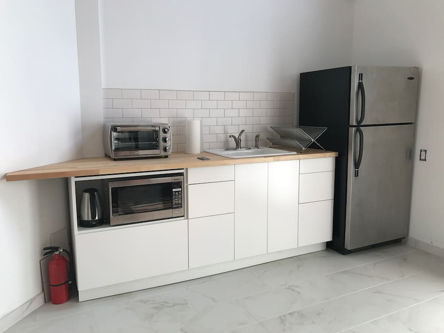 New kitchen with microwave, toaster oven hotplate and kettle.
