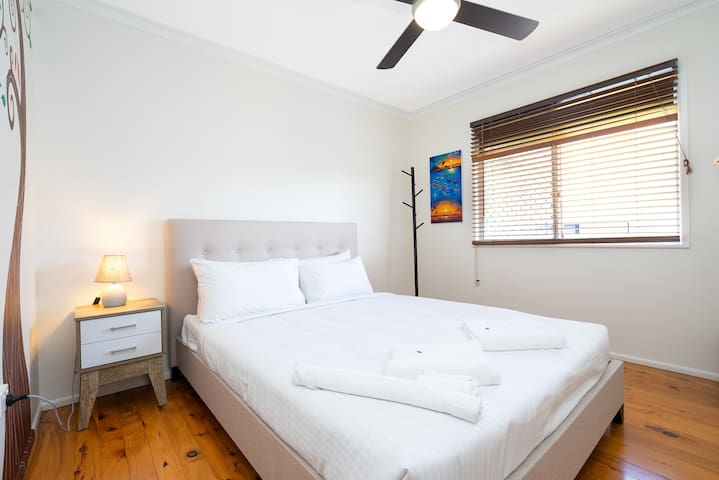Discover a third bedroom with a queen bed, hotel quality linen and direct access to the plush garden and outdoor decks
