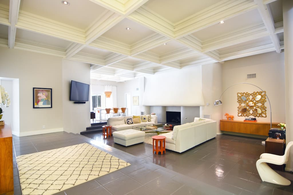 """A grand entrance: 15 ft coffered ceiling, sunken living room, natural gas fire place and a 60"""" television. Quintessential Palm Springs."""