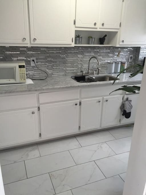 Marble counter-tops, modern white kitchen with glass backsplash