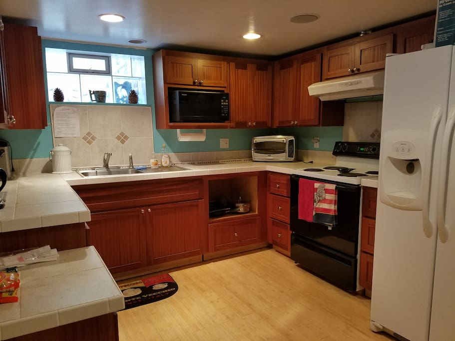Full kitchen with fridge, stove, microwave, & toaster oven.