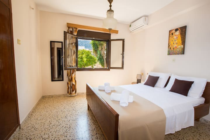 Bedroom with queen double bed and garden-mountain view.