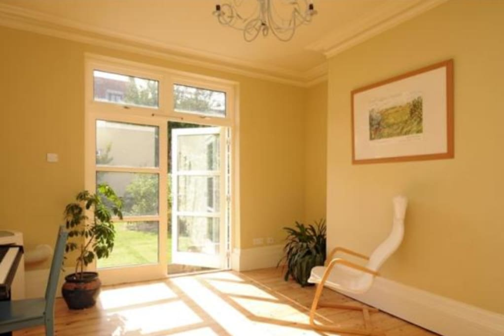 Sunny dining room with doors opening to the garden