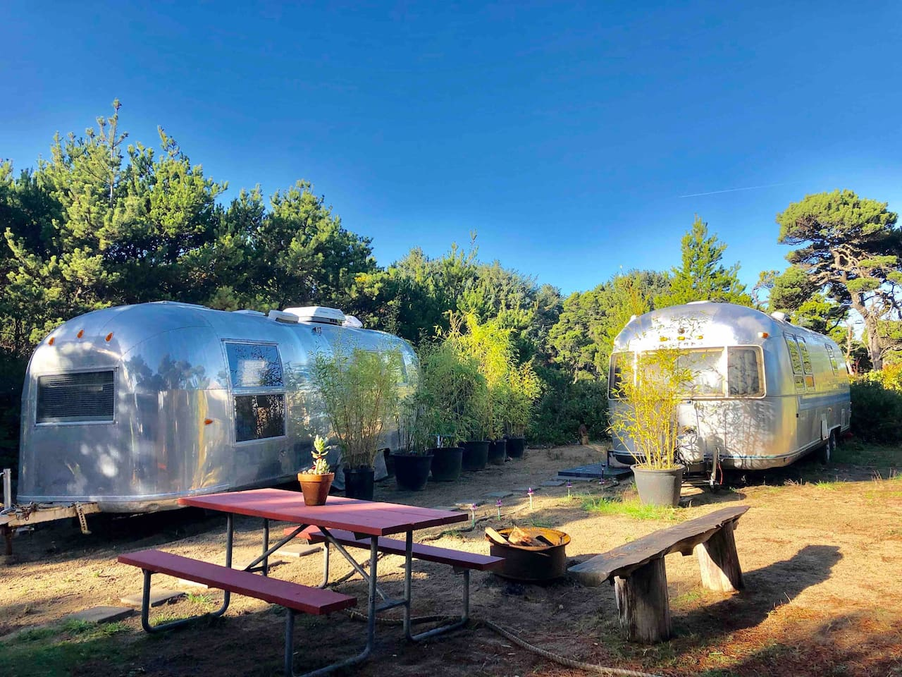 """Welcoming to camp the 64 Airstream Land Yacht! (Pictured on the left) Comfy and bright inside. Private entrance, under the shore pines with bench and charcoal grill. Relax to the sounds of the surf just one block away via the magical """"hobbit trail""""."""